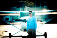 high school senior boy photographed with air plane at maine jetport in portland
