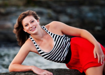 girl in red skirt on rock in water for senior photos at beach in maine