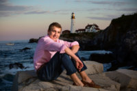 boy sitting on rocks in front of light house at fort williams for senior pictures