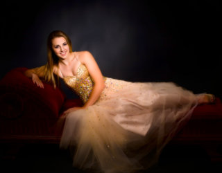 girl wearing prom dress photographed on red lounge in studio