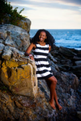 girl in black and white striped dress on rocks by ocean for senior photos