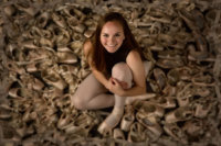 senior girl photographed in sea of her old ballet tap shoes in studio in maine