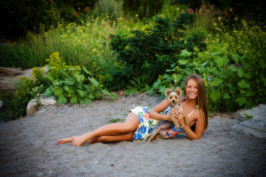 senior girl with dog on sand at beach in maine