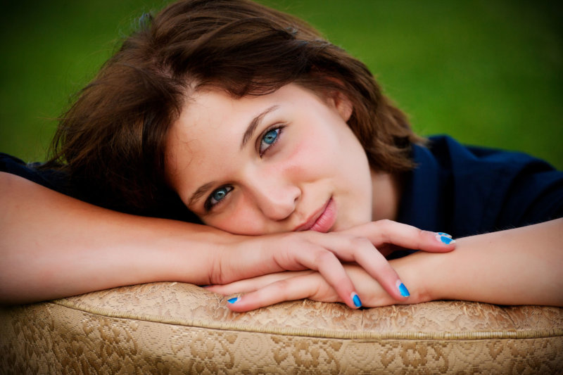 senior girl in relaxed yearbook photo taken in park on chair