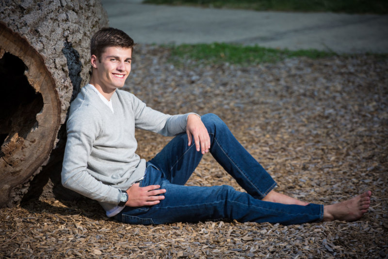 senior guy sits on wood chips and leans against tree trunk in park photo shoot