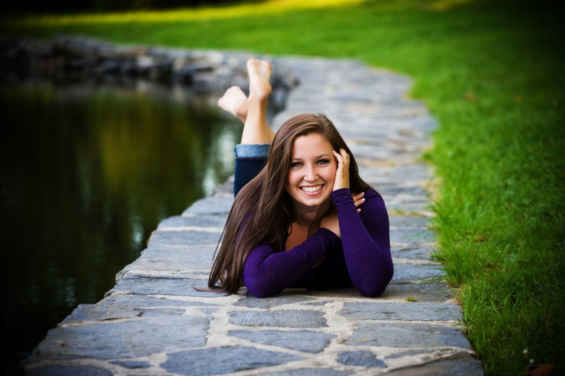 girl with purple sweater lays alongside pond at park in senior photo shoot