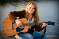 senior girl playing guitar above ocean