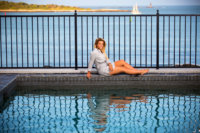 girl in gray dress photographed at pool in front of bay in senior photo shoot at her house