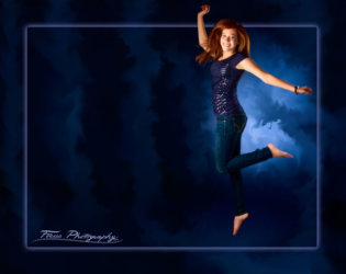jumping girl photographed on blue back ground in senior photography studio