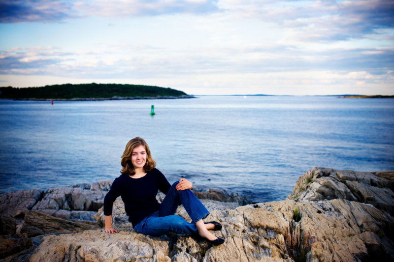 senior girl on rocks in front of ocean in fort williams park in maien