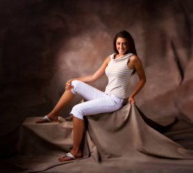 girl wearing white pants photographed on brown set for senior pictures in photography studio in Maine