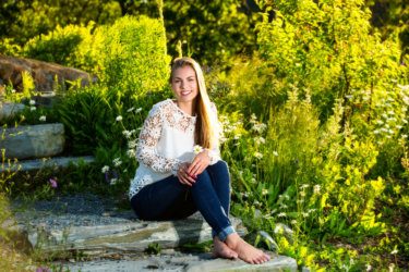 barefoot girl among daisies in fort williams park for senior pictures