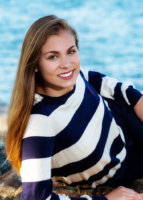 senior picture taken at beach with striped shirt and water behind her