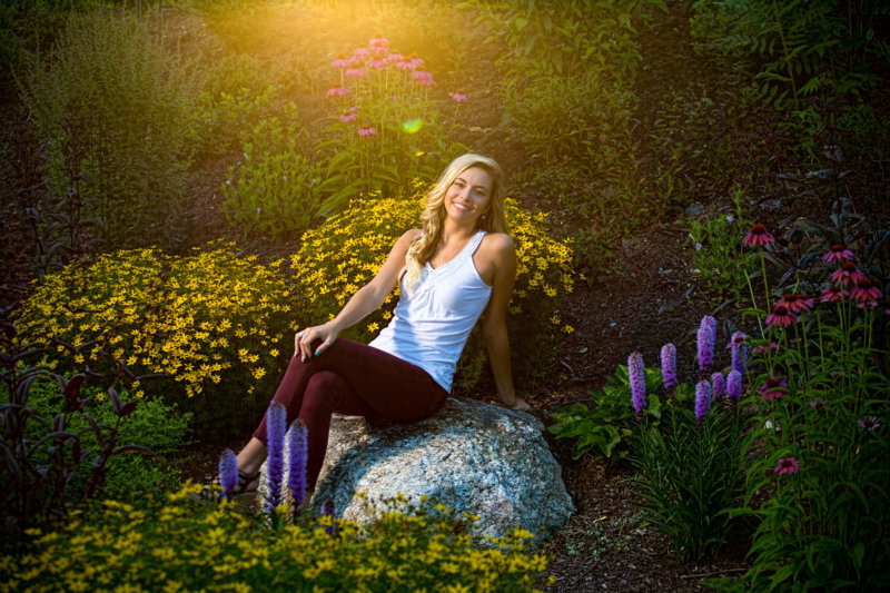 senior girl at sunset photographed among flowers at fort williams for senior pictures
