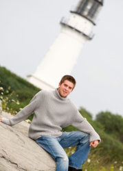 senior boy wearing gray sweater sits in front of lighthouse for graduation portrait