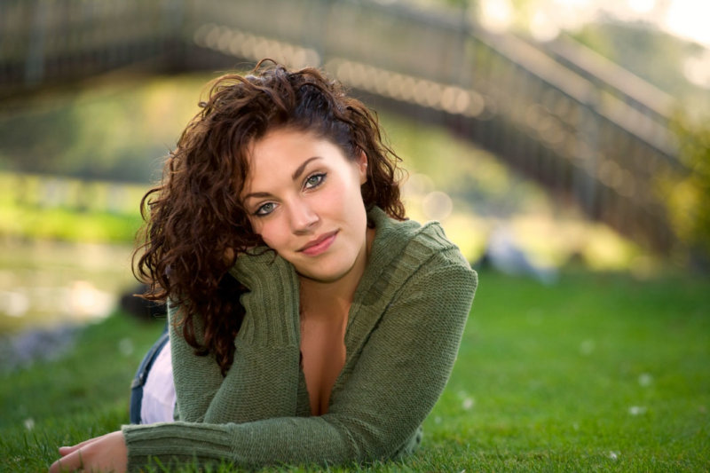senior girl in park setting wearing green sweater on grass