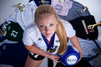 volleyball player and her uniforms and awards for senior photo shoot in Maine photography studio