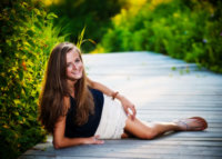 Kiera laying on beach boardwalk for senior pictures