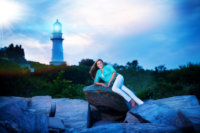senior portrait of girl in white pants and teal top in front of lighthouse in Maine