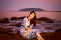 girl with pretty dress photographed at ocean for senior pictures in maine