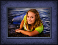 senior girl laying on sand in water at beach