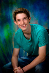 senior boy in green shirt photographed in studio for graduation picture