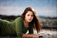 senior girl laying on sandy beach in maine for twelfth year pics