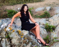 graduating senior photographed in black dress on rocks at beach in maine