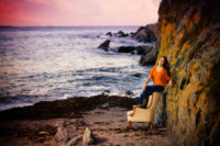 senior picture of girl at beach in orange shirt on top of yellow chair with rocks behind her and ocean in background