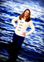 senior in ocean at beach wearing ivory sweater and blue jeans