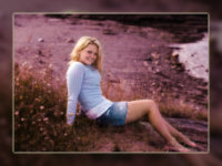 senior girl wearing blue sweater on cliff over beach in maine