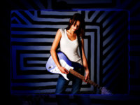 girl holds guitar in front of striped wall