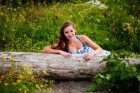 wildflowers and driftwood surround senior girl in maine