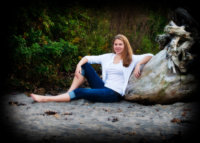 senior girl wearing blue jeans and white sweater reclines on driftwood at beach in maine