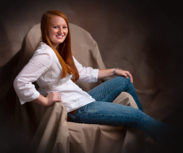 red haired girl on chair in brown set in photography studio