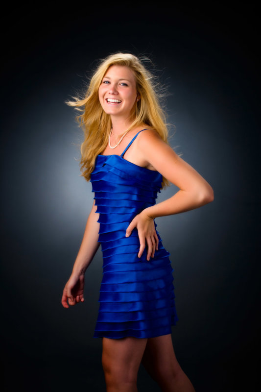 girl with blue dress and gray paper background for senior photo