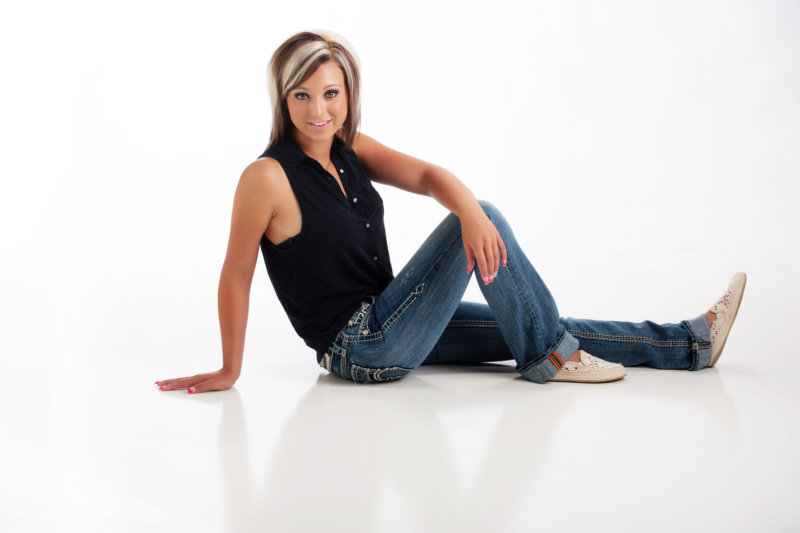 girl in jeans and black top on white in senior photo studio