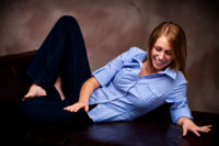 girl on brown couch in senior picture studio in maine