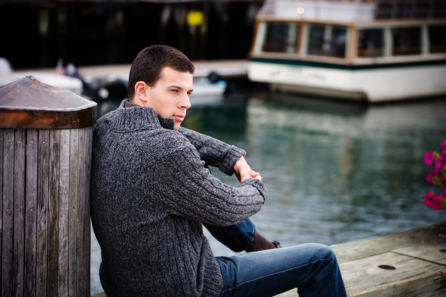 senior guy in gray sweater sitting on waterfront of portland