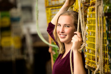 senior girl poses with lobster traps during photo shoot in portland, maine