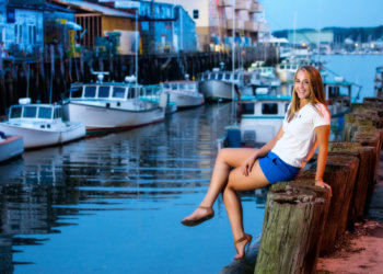 girl sits on wooden pilings at waterfront of portland for senior photo shoot