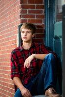 senior boy photographed in doorway in downtown portland