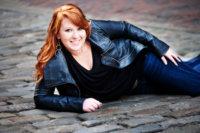 girl in leather jacket lying on cobblestone street in portland for senior portrait shoot
