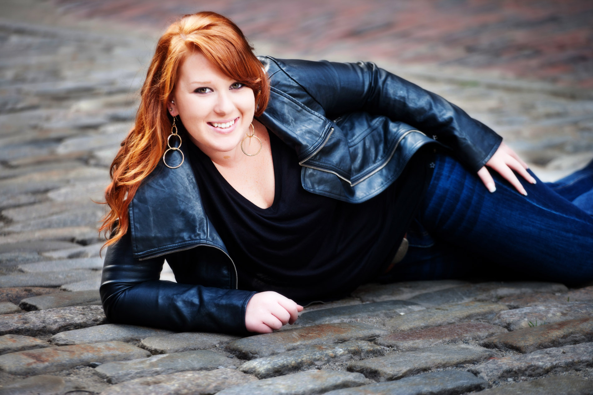 girl in leather jacket lying on cobblestone street in portland for senior portrait shoot