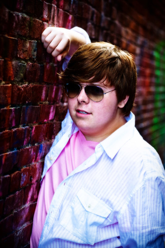 senior boy leans on colorful brick wall in alley