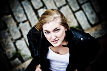 girl in leather jacket photographed above cobblestones in high school senior pictures photo shoot in maine