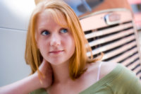 senior portrait of girl leaning on truck in city location