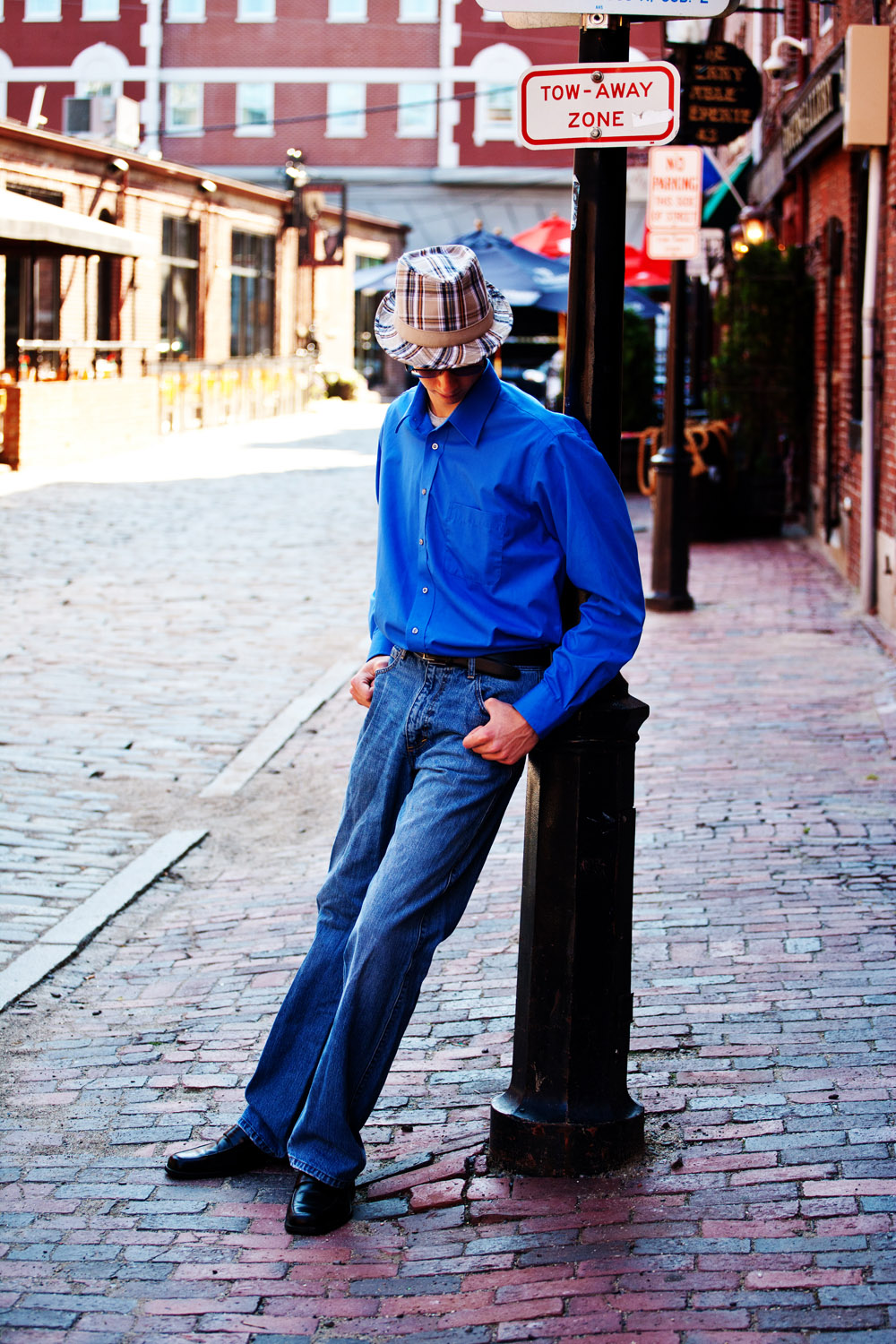 urban portrait of senior boy wearing plaid hat leaning on light post