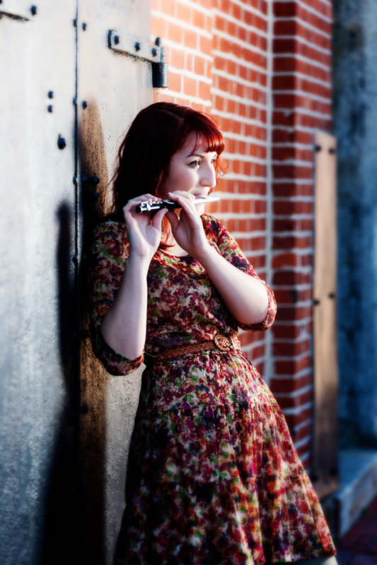 girl playing flute leaning on door in downtown portland
