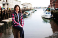 girl in red plaid shirt and vest photographed in front of docks in portland, maine for senior photos